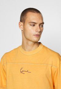 Karl Kani - SMALL SIGNATURE WASHED TEE UNISEX  - Triko spotiskem - yellow - 4