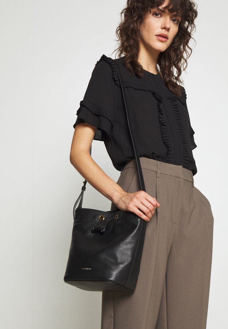 Coccinelle - LEA BUCKET BAG - Across body bag - noir