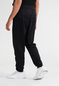 Under Armour - SPORTSTYLE - Tracksuit bottoms - black - 2