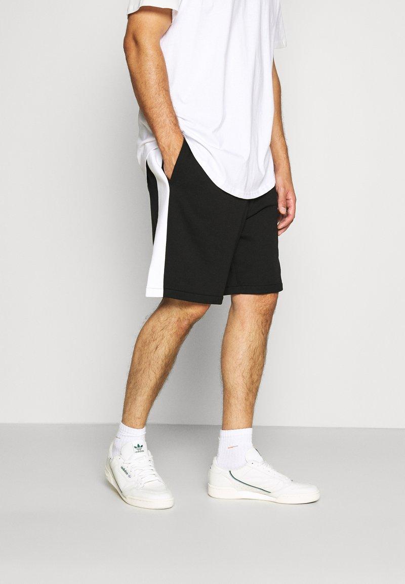 Lacoste - Pantalon de survêtement - noir/blanc