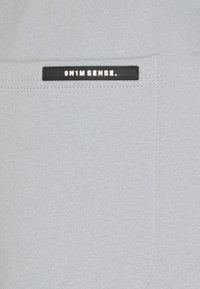 9N1M SENSE - LOGO PANTS UNISEX - Tracksuit bottoms - pantone grey - 7