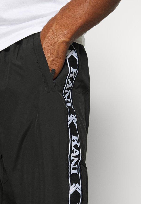 Karl Kani TAPE TRACKPANTS - Spodnie treningowe - black/czarny Odzież Męska MQAB
