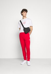 adidas Originals - UNISEX - Tracksuit bottoms - scarle/white - 1