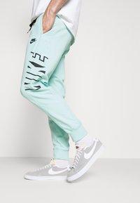 Nike Sportswear - Tracksuit bottoms - light dew/black - 3