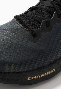 Under Armour - CHARGED PULSE - Zapatillas de running neutras - black/metallic gold - 5
