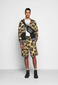 Versace Jeans Couture - PRINT NEW LOGO - Pantaloni sportivi - nero - 1