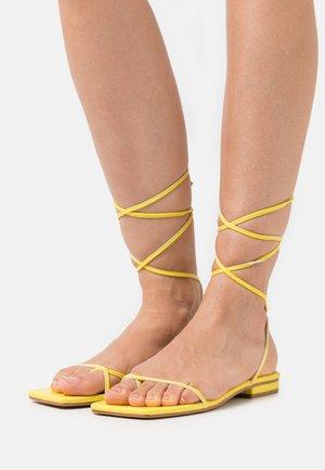 DOLLI - T-bar sandals - yellow