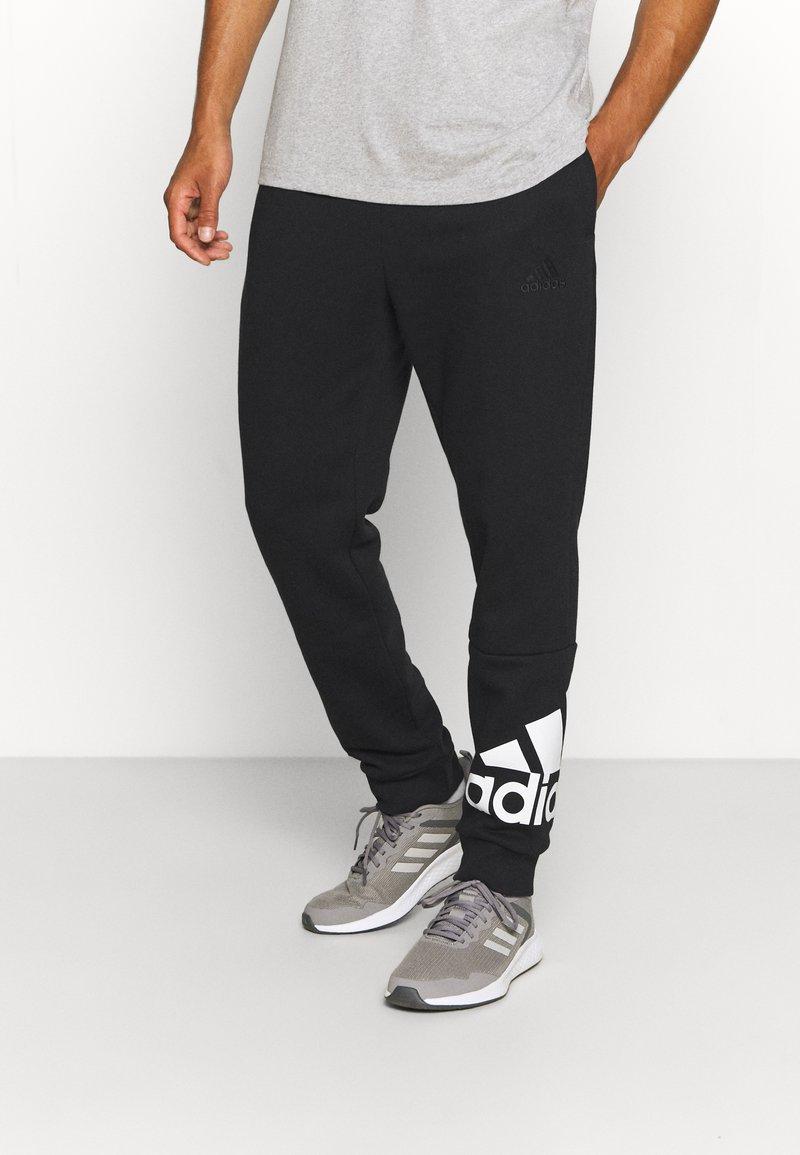 adidas Performance - ESSENTIALS - Tracksuit bottoms - black/white