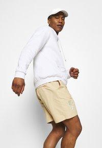 adidas Originals - WOVEN UNISEX - Shorts - hazy beige - 3