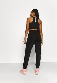 Puma - REBEL HIGH WAIST PANTS  - Pantalones deportivos - puma black untamted - 2
