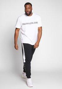Calvin Klein - LOGO STRIPE  - Tracksuit bottoms - black - 1