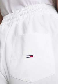 Tommy Jeans - JOGGER TAPE RELAXED - Tracksuit bottoms - white - 4