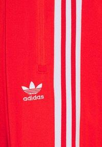adidas Originals - BECKENBAUER UNISEX - Tracksuit bottoms - red - 5