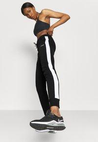 Fila - LAKI PANTS - Spodnie treningowe - black/bright white - 3