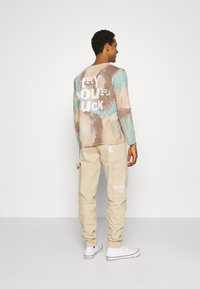 Karl Kani - RINSE BLOCK PANTS - Relaxed fit jeans - beige - 2