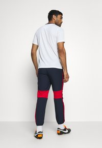 Nike Performance - DRY ACADEMY PANT - Tracksuit bottoms - obsidian/university red/white - 2
