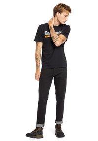 Timberland - Print T-shirt - black-wheat boot - 1