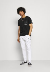 Nike Sportswear - REPEAT - Tracksuit bottoms - white/black - 1