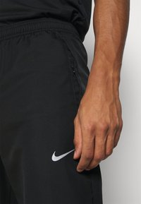 Nike Performance - ESSENTIAL PANT - Tracksuit bottoms - black/reflective silver - 4