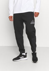 adidas Performance - ESSENTIALS RELAXED - Tracksuit bottoms - black - 0