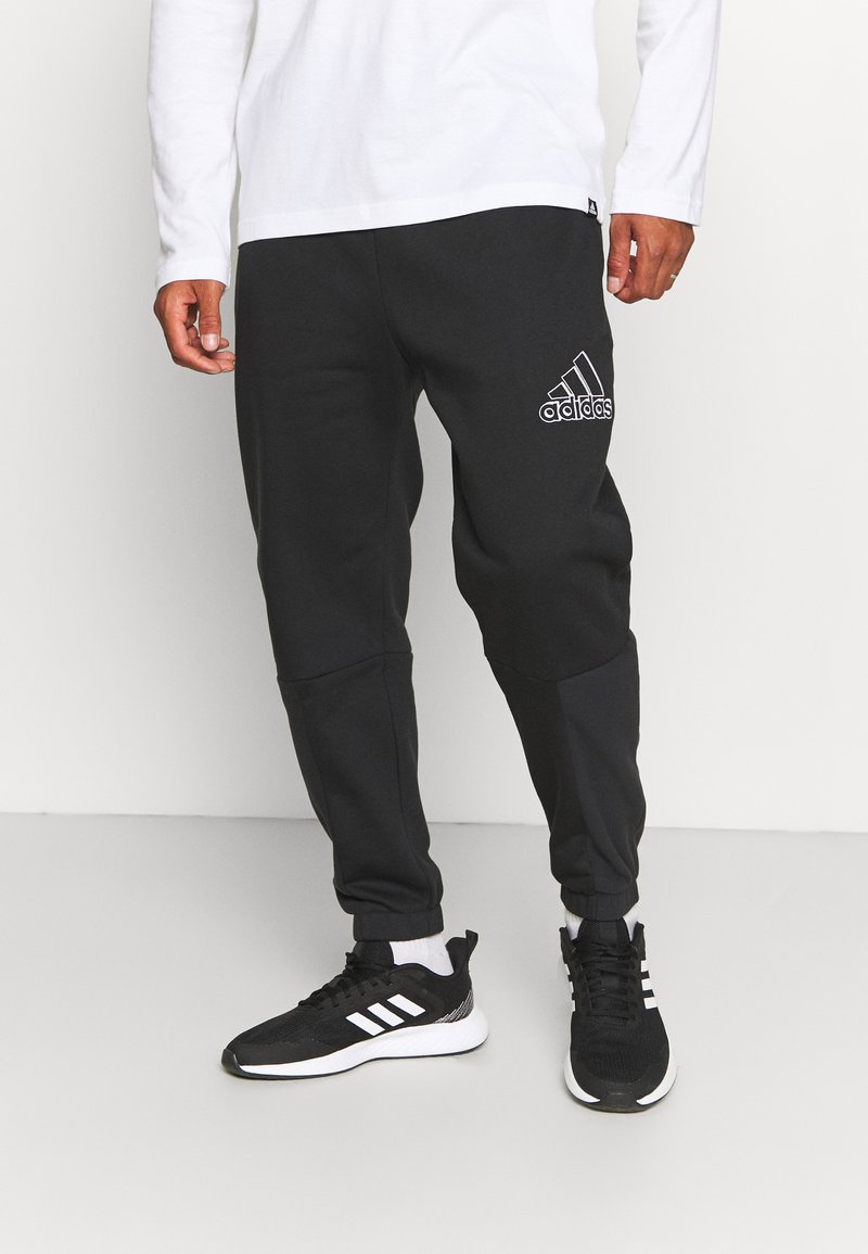 adidas Performance - ESSENTIALS RELAXED - Tracksuit bottoms - black