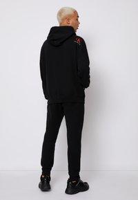Calvin Klein Jeans - OVERSIZED LARGE BADGE HOODIE UNISEX - Sweatshirt - black - 2