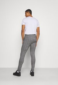 11 DEGREES - PRINCE OF WALES JOGGER - Tracksuit bottoms - black/white - 2
