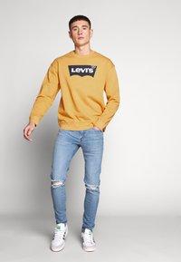 Levi's® - RELAXED GRAPHIC CREWNECK - Sweatshirt - golden apricot - 1