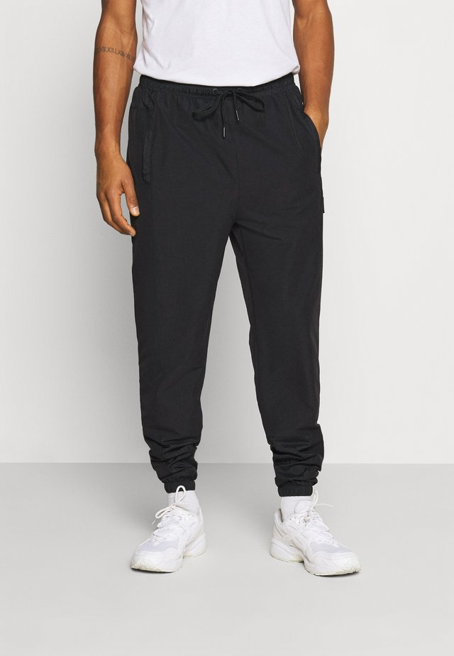 STOREO - Tracksuit bottoms - black