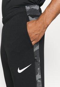 Nike Performance - CAMO - Tracksuit bottoms - black/white - 4