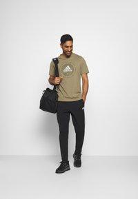 adidas Performance - UNIVERSAL - T-shirt med print - cargo - 1