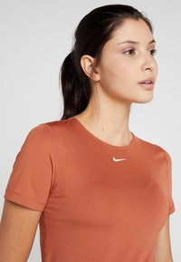 Nike Performance - ALL OVER - Basic T-shirt - dusty peach/echo pink