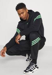 adidas Originals - TRACK PANT UNISEX - Tracksuit bottoms - black/shock lime - 3