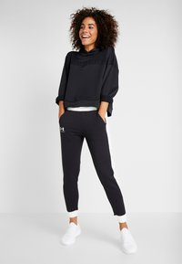 Under Armour - RIVAL GRAPHIC NOVELTY PANT - Tracksuit bottoms - black/onyx white - 1