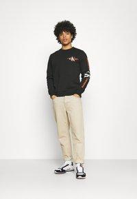 Calvin Klein Jeans - URBAN GRAPHIC LOGO CREW NECK UNISEX - Collegepaita - black - 1