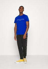 Tommy Hilfiger - BASIC BRANDED - Tracksuit bottoms - black - 1
