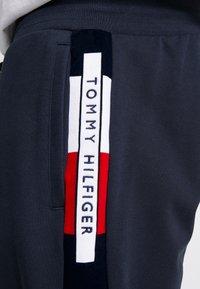 Tommy Hilfiger - FLOCKED - Tracksuit bottoms - blue - 4