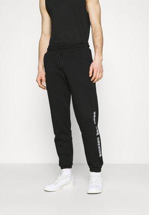 GOTHIC BRANDING - Teplákové kalhoty - black
