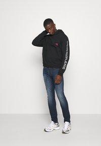 Calvin Klein Jeans - MOTO  - Felpa con cappuccio - black - 1