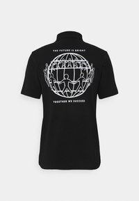Tommy Hilfiger - ONE PLANET BACK LOGO UNISEX - Polo shirt - black - 6