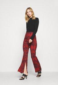 Milk it - TROUSER FRONT SPLIT DETAIL - Trousers - red/black - 1
