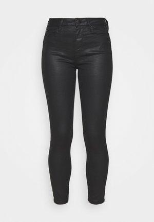 SOFT SKINNY COATED - Trousers - black