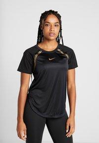 Nike Performance - TOP GLAM - T-shirt z nadrukiem - black/metallic gold - 0