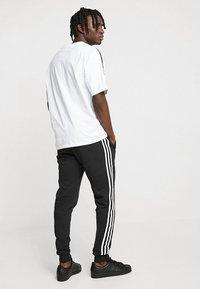 adidas Originals - STRIPES PANT UNISEX - Pantalon de survêtement - black - 2