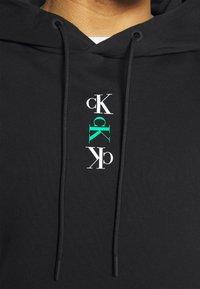 Calvin Klein Jeans - REPEAT TEXT GRAPHIC HOODIE UNISEX - Hoodie - black - 4
