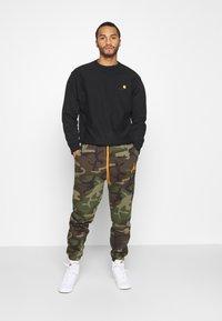 Jordan - JUMPMAN AIR CAMO PANT - Pantaloni sportivi - medium olive/total orange - 1