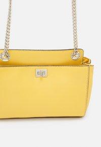 Guess - SANDRINE CONVERTIBLE CROSSBODY - Across body bag - yellow - 4