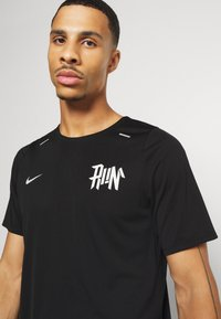 Nike Performance - RISE - T-shirt med print - black/light bone/reflective silver - 3