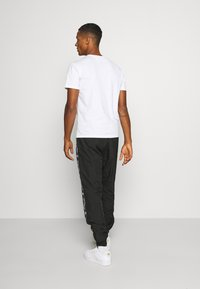 Karl Kani - TAPE TRACKPANTS - Trainingsbroek - black - 2