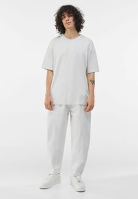 Bershka - LOOSE FIT - Trousers - white - 1